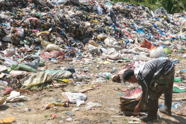 A scavenger collects reusable plastic from the illegal open dumpsite in Malapatan town in the southern Philippines. Image by Bong S. Sarmiento.