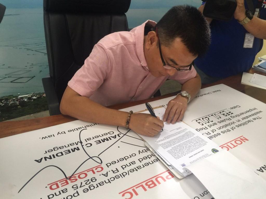 LLDA General Manager Jaime Medina signs cease and desist orders for violators of RA 9275. photo by LLDA