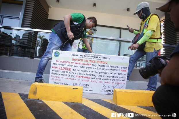 LLDA personnel put up a 'notice of violation' in one of the establishments along Manila Bay. photo by DENR