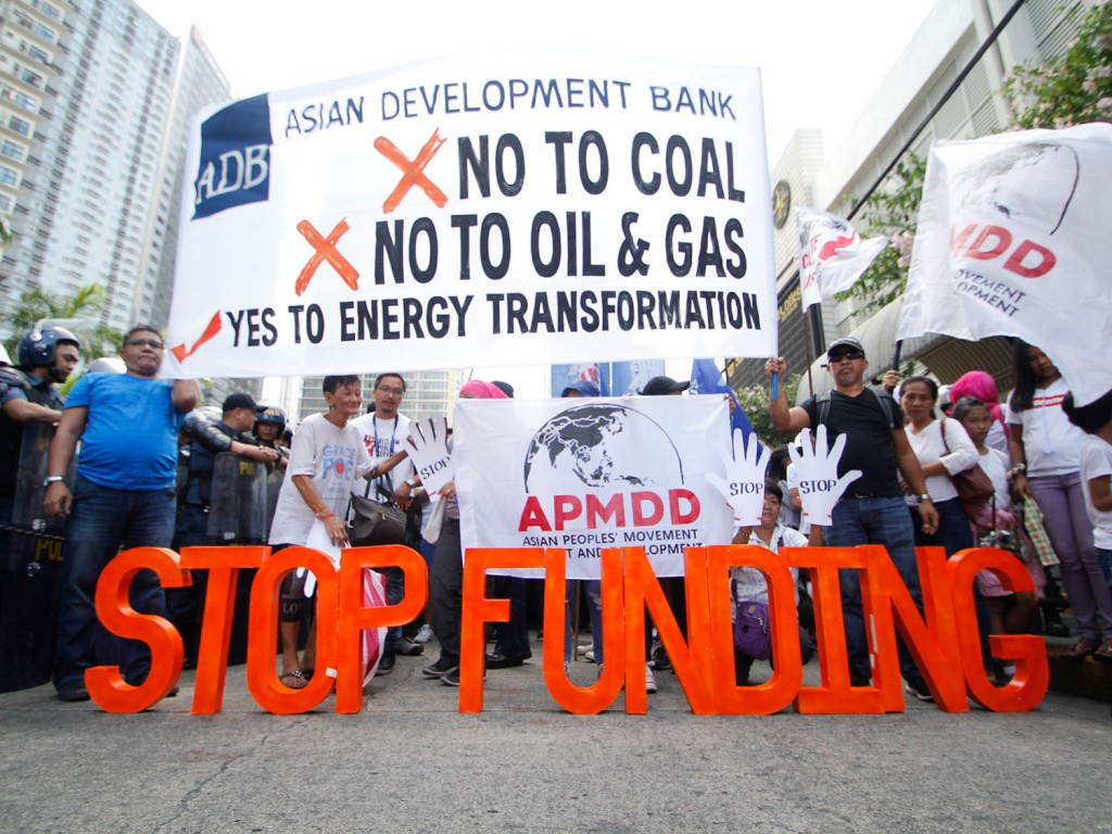 Police officers block climate activists protesting in front of the headquarters of Asian Development Bank during the annual meeting of the board of governors on May 4, 2018. They are calling to stop funding dirty energy sources and start supporting renewable energy in Asia. Image by AC Dimatactac/350 Pilipinas
